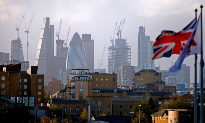 """A Union flag flies from a pole as construction cranes stand near skyscrapers in the City of London, including the Heron Tower, Tower 42, 30 St Mary Axe commonly called the """"Gherkin"""", the Leadenhall Building, commonly called the """"Cheesegrater"""", as they are pictured beyond blocks of residential flats and apartment blocks, from east London on Oct. 21, 2017. / AFP PHOTO / Tolga AKMEN        (Photo credit should read TOLGA AKMEN/AFP/Getty Images)"""