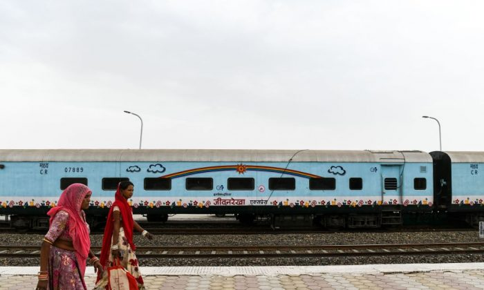 In this photograph taken on April 13, 2018, Indian women walk past the Lifeline Express at a railway station in Jalore in India's western state of Rajasthan. (CHANDAN KHANNA/AFP/Getty Images)