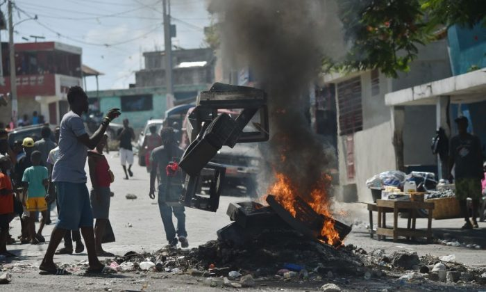 A demonstrator throws plastics onto a smoldering barricade in central Port-au-Prince, July 9, 2018, following two days of deadly looting and arson triggered by a quickly-aborted government attempt to raise fuel prices. (HECTOR RETAMAL/AFP/Getty Images)