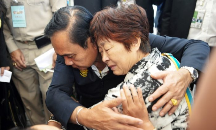 Thailand's Prime Minister Prayuth Chan-ocha comforts a relative of Chinese tourists involved in a sunken tourist boat accident at a hospital in Phuket, Thailand, on July 9, 2018. (Sooppharoek Teepapan/Reuters)