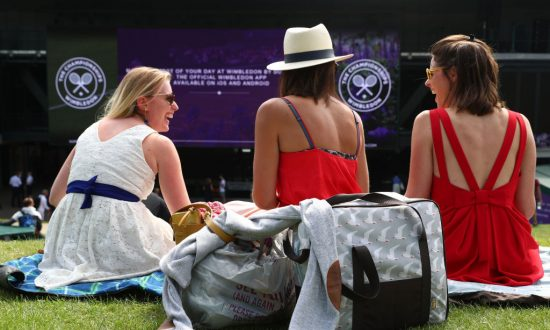 Tennis fans sit on Murray Mound above the big screen in the grounds of Wimbledon All England Tennis Clubs in London, on July 4, 2018. (Matthew Lewis/Getty Images)