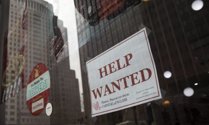 """A """"help wanted"""" sign hangs on a window of a restaurant in Lower Manhattan, May 4, 2018 in New York City. (Drew Angerer/Getty Images)"""