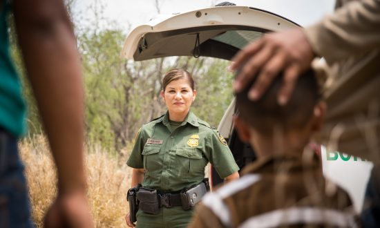 Border Patrol agent Marlene Castro speaks to a group of illegal immigrants and children who just crossed into the United States from Mexico, in Hidalgo County, Texas, on May 26, 2017. (Benjamin Chasteen/The Epoch Times)
