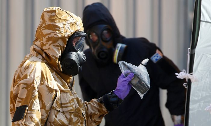 Forensic investigators wearing protective suits emerge from the rear of John Baker House in Amesbury, United Kingdom, on July 6, 2018. (Reuters/Henry Nicholls/File Photo)