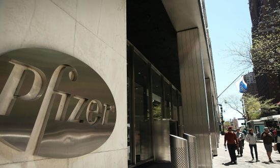 People walk past the Pfizer logo on their world headquarters in Manhattan, New York City, on May 5, 2014. (Spencer Platt/Getty Images)