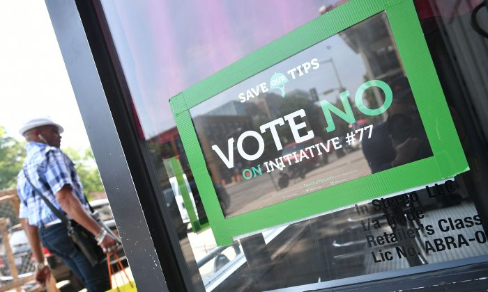 """A man walks by a """"vote no on Initiative #77"""" poster on June 18, 2018 in Washington. (MANDEL NGAN/AFP/Getty Images)"""