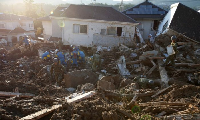 Rescue workers and Japan Self-Defense Forces soldiers search for missing people at a landslide site caused by heavy rain in Kumano Town, Hiroshima Prefecture, Japan July 11, 2018. (Reuters/Issei Kato)
