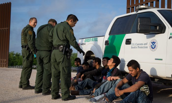 Border Patrol agents apprehend illegal immigrants shortly after they crossed the border from Mexico into the United States in the Rio Grande Valley Sector near McAllen, Texas, on March 26, 2018. (LOREN ELLIOTT/AFP/Getty Images)