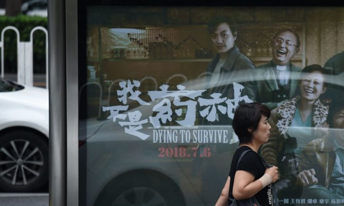 """A woman walks past a poster of the film """"Dying to Survive"""" at a bus stop in Beijing on July 12, 2018. (Wang Zhao/AFP/Getty Images)"""