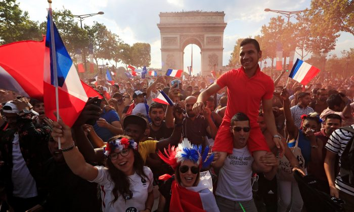 France fans react on the Champs-Elysees avenue after they defeated Croatia in their Soccer World Cup final match on July 15, 2018.   (Reuters/Gonzalo Fuentes)