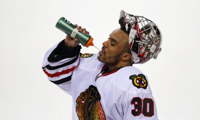 Ray Emery has a drink of water during a break in their game against the Calgary Flames during the third period of their NHL hockey game in Calgary, Alberta, Feb. 2, 2013. (REUTERS/Todd Korol)