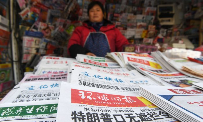 A newsstand vendor with state-run newspapers on sale, in Beijing on December 6, 2016. (Greg Baker/AFP/Getty Images)