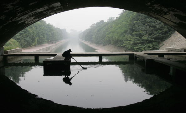 A worker gathers rubbish on the moat around the Old City Wall in Xian of Shaanxi Province, on August 23, 2006. (China Photos/Getty Images)