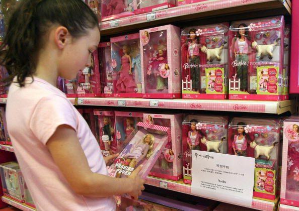 "A young girl holds a Barbie doll next to a notice saying that the toy ""Barbie and Tanner"" made by US toy giant Mattel, which has just been recalled in the US, is out of stock at a Toys ""R"" Us store in Shanghai, Aug.15 2007.  (Photo credit should read MARK RALSTON/AFP/Getty Images)"