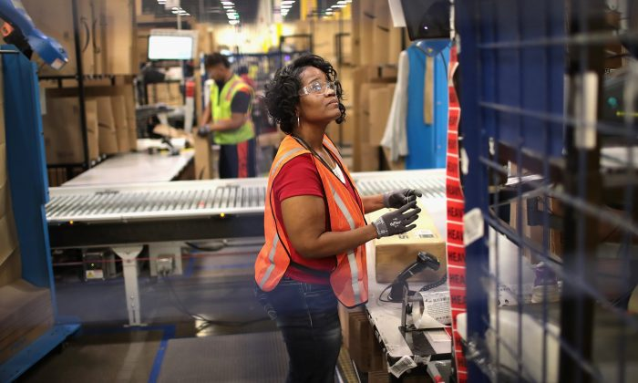 Workers pack and ship customer orders at an Amazon fulfillment center in Romeoville, Ill., Aug. 1, 2017. (Scott Olson/Getty Images)