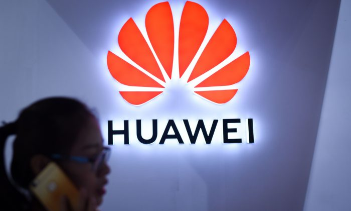 A woman uses her mobile phone in front of a LED display board of Huawei at the Beijing International Consumer Electronics Expo in Beijing on July 9, 2018. (Wang Zhao/AFP/Getty Images)