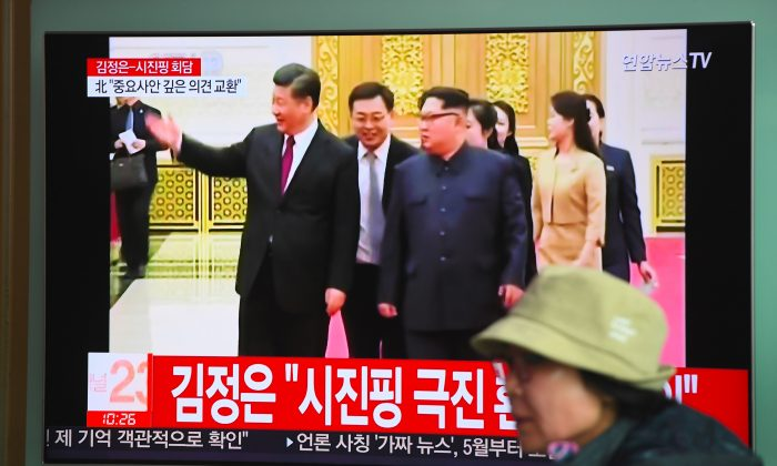 A woman walks past a television news screen reporting about a visit to China by North Korean leader Kim Jong Un, at a railway station in Seoul on March 28, 2018. During the visit, just prior to Kim's summit with President Donald Trump, Chinese leader Xi Jinping (pictured with Kim) showered the North Korean dictator with nearly $400,000 in gifts, violating U.N. sanctions.  (JUNG YEON-JE/AFP/Getty Images)