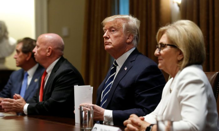 President Donald Trump sits between Rep. Kevin Brady (R-Texas) and Rep. Diane Black (R-Tenn.) after speaking about his summit with Russian President Vladimir Putin at the start of a meeting with members of the U.S. Congress at the White House on July 17, 2018. (REUTERS/Leah Millis)