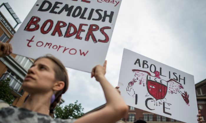 People hold up signs as they protest the U.S. Immigration and Customs Enforcement agency (ICE) and the recent detentions of illegal immigrants, in Washington, on July 16, 2018. (ANDREW CABALLERO-REYNOLDS/AFP/Getty Images)