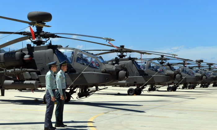 Two Taiwan servicemen stand in front of U.S.-made Apache AH-64E attack helicopters during a commissioning ceremony at a military base in Taoyuan City, Taiwan, on July 17, 2018. (Sam Yeh/AFP/Getty Images)