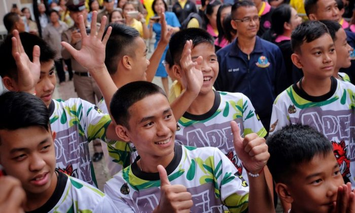 """Adul Sam-on (Center), the stateless boy who spoke to the British diver in English during their rescue, arrive for a press conference with eleven other boys and their coach from the """"Wild Boars"""" soccer team. (Linh Pham/Getty Images)"""