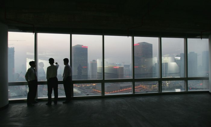 Office workers look out at the Central Business District in Beijing from inside a newly developed office building on Nov. 18, 2004. (Cancan Chu/Getty Images)