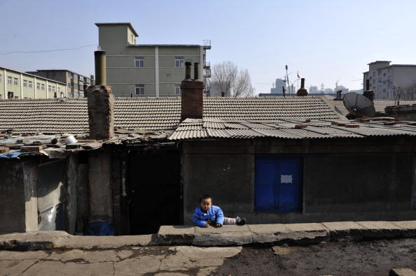 A child plays at a shanty town in Shenyang City, Liaoning Province, China, on March 11, 2009. (China Photos/Getty Images)