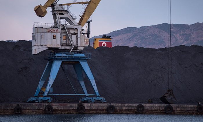 A mountain of North Korean coal, stranded by a UN ban on coal exports from North Korea, is piled up on one side of the barrier in Rajin Port, North Korea, on November 21, 2017. (ED JONES/AFP/Getty Images)