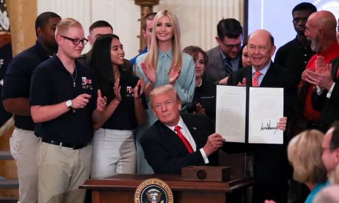 "President Donald Trump signs an executive order during the ""Pledge to America's Workers"" event in the East Room of the White House on July 19, 2018. (Samira Bouaou/The Epoch Times)"