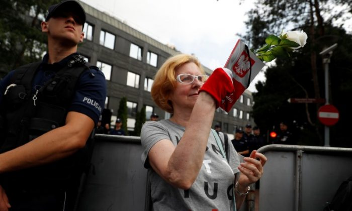A woman holds a copy of the Polish constitution as she takes part in a protest in support of free courts outside the Parliament building in Warsaw July 18, 2018. (REUTERS/Kacper Pempel)