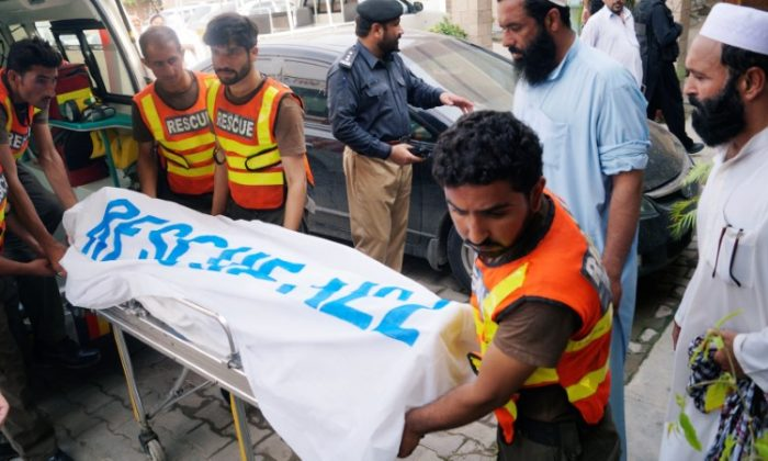 Rescue workers move the body of Ikramullah Gandapur, a candidate of the Pakistan Tehreek-e-Insaf (PTI), or Pakistan Justice Movement, who was killed in a suicide attack in the northwestern province of Khyber Pakhtunkhwa, outside hospital morgue in Dera Ismail Khan, Pakistan July 22, 2018. (Reuters/Stringer)