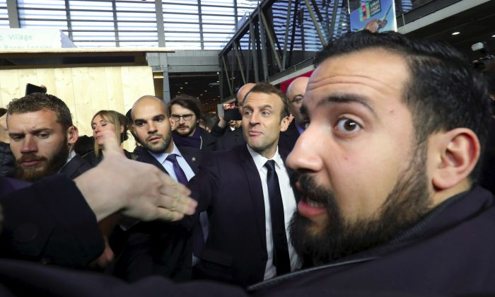 French President Emmanuel Macron shakes hands while visiting the 55th International Agriculture Fair, as Elysee senior security officer Alexandre Benalla (R) looks on at the Porte de Versailles exhibition center in Paris, France, Feb. 24, 2018. (Ludovic Marin/Pool via Reuters)