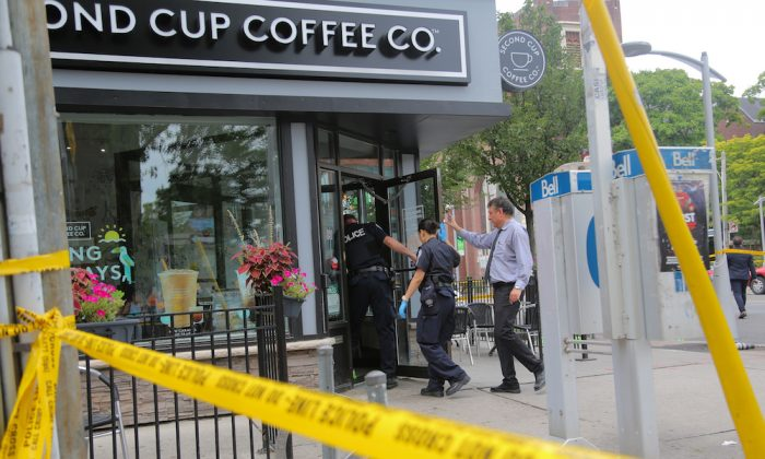 Police officers enter a coffee shop damaged by gunfire while investigating a mass shooting on Danforth Avenue in Toronto, Canada, July 23, 2018.  (Reuters/Chris Helgren)