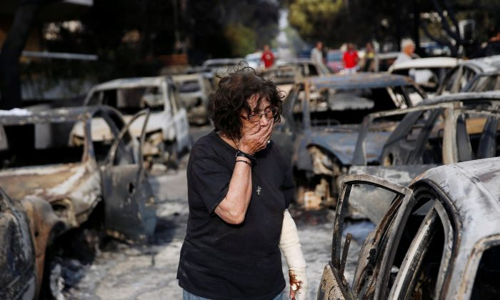 A woman reacts as she tries to find her dog, following a wildfire at the village of Mati, near Athens, Greece July 24, 2018. (Reuters/Costas Baltas)
