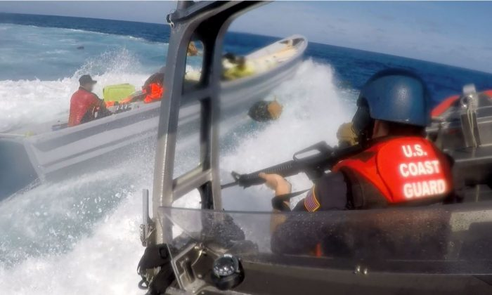A U.S. Coast Guardsman aboard an interceptor boat launched from the Coast Guard Cutter Steadfast pursues a suspected smuggling vessel as the suspected smugglers throw bales overboard during a high-speed chase in international waters of the Eastern Pacific Ocean July 11, 2018. (U.S. Coast Guard photo)
