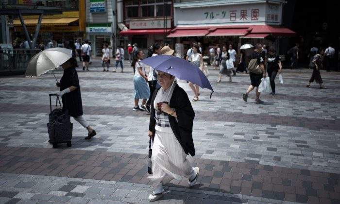A woman holds an umbrella as she walks along a street in Tokyo on July 23, 2018, as Japan suffers from a heatwave. (Martin Bureau/AFP/Getty Images)