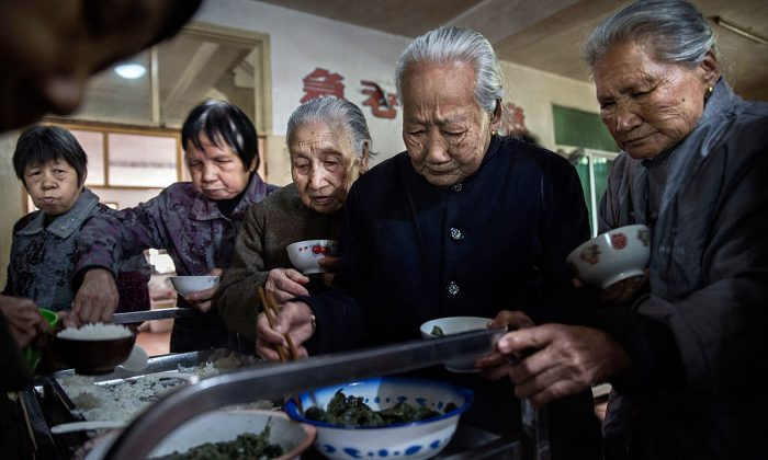 Elderly Chinese people serve themselves lunch at a nursing home in Sha County, Fujian Province, China, on March 17, 2016. (Kevin Frayer/Getty Images)