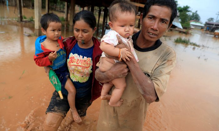 Parents carry their children as they leave their home during the flood after the Xepian-Xe Nam Noy hydropower dam collapsed in Attapeu province, Laos  July 26, 2018. (Retuers/Soe Zeya Tun)