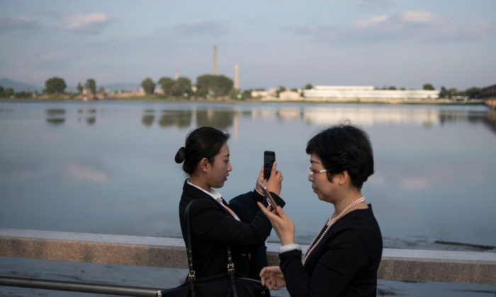 People take pictures by the Yalu River in the border city of Dandong, in China's northeast Liaoning Province, on May 30, 2018. (Fred Dufour/AFP/Getty Images)