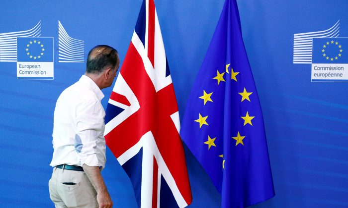 An official inspects a Union Jack flag next to the European Union flag, ahead of a meeting between Britain's Secretary of State for Exiting the European Union Dominic Raab and European Union's chief Brexit negotiator, Michel Barnier, at EU Commission headquarters in Brussels, Belgium, July 19, 2018. (François Lenoir/Reuters)