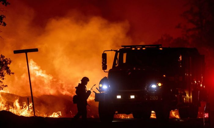TOPSHOT - A firefighter lights backfires during the Carr fire in Redding, California on July 27, 2018. - One person has died and at least two others have been injured as wind-whipped flames tore through the region. (Photo by JOSH EDELSON / AFP)        (Photo credit should read JOSH EDELSON/AFP/Getty Images)