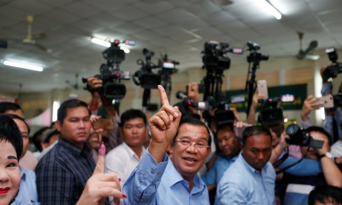 Cambodia's Prime Minister and President of the Cambodian People's Party (CPP) Hun Sen and his wife Bun Rany show their stained fingers at a polling station during a general election in Takhmao, Kandal province, Cambodia July 29, 2018. (Reuters/Samrang Pring)