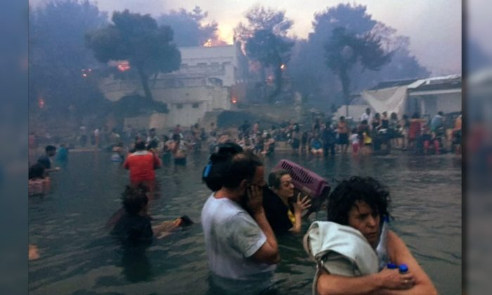 Dozens of people flee into the sea to escape wildfires sweeping through the Greek resort of Mati, on July 23, 2018. (Elia Kallia via Reuters)