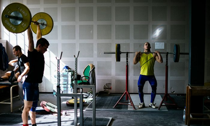 Athletes lift weights during a training session at the Bulgaria's national weightlifting centre in Sofia on March 26, 2016.