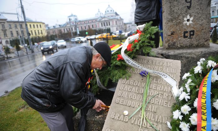 A man light candles during a commemoration ceremony in Bucharest on Dec. 21, 2011, next to a stone bearing names of people killed by communist regime forces in 1989. (Daniel Mihailescu/AFP/Getty Images)