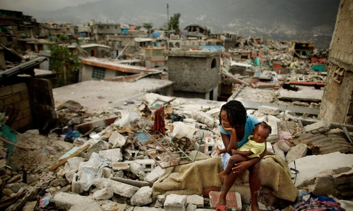 Sherider Anilus, 28, and her daughter, 9-month-old Monica, sit on the spot where her home collapsed during 2010's 7.0 earthquake in Port-au-Prince, Haiti. (Chip Somodevilla/Getty Images)