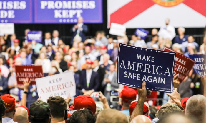 Audience members hold up signs at President Donald Trump's Make America Great Again rally in Tampa, Fla., on July 31, 2018. (Charlotte Cuthbertson/The Epoch Times)