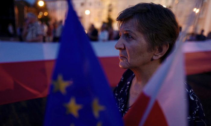 A woman holds flags during an anti-government protest in support of free courts in front of the Supreme Court building in Warsaw, Poland July 27, 2018. (Reuters/Kacper Pempel)