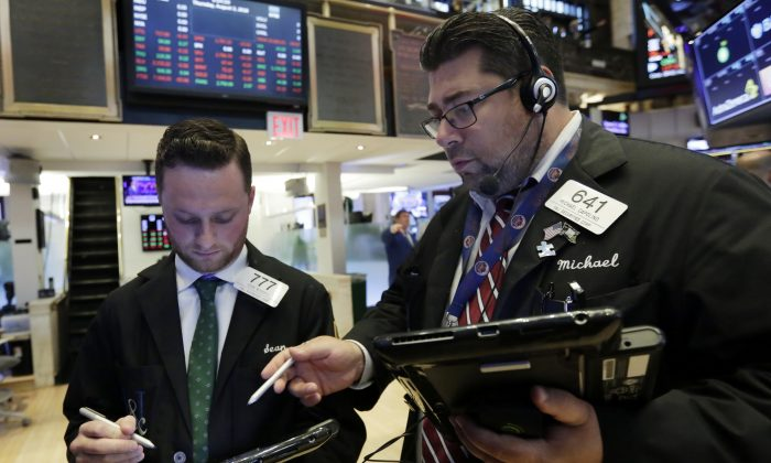Traders Sean Russell (L) and Michael Capolino confer as they work on the floor of the New York Stock Exchange on Aug. 2, 2018. (AP Photo/Richard Drew)