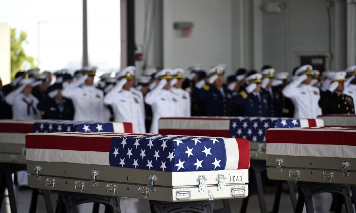 Flag-draped transfer cases with the remains of American soldiers repatriated from North Korea during a repatriation ceremony after arriving to Joint Base Pearl Harbor-Hickam, Honolulu, Hawaii, on Aug. 1, 2018. (RONEN ZILBERMAN/AFP/Getty Images)